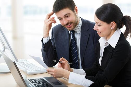 Two business people sitting with open laptop, computer and discussing questions